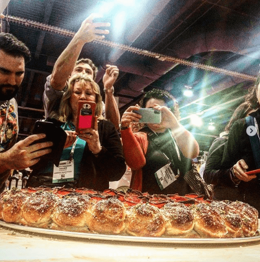 group of people taking photos of a pizza